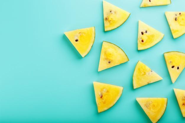 Plastry świeżego żółtego arbuza na niebiesko