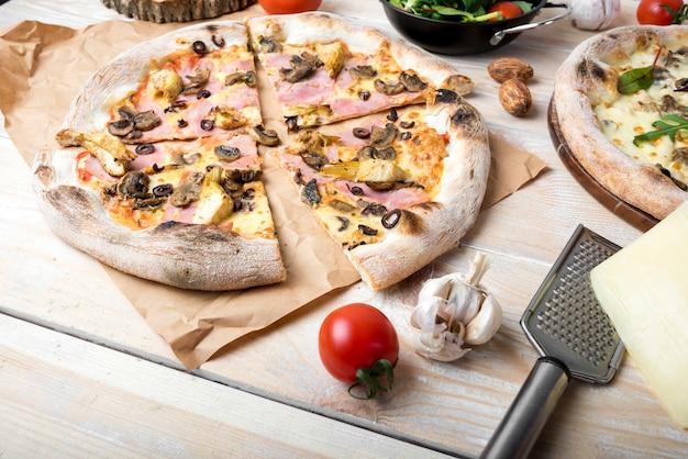 Plastry świeżej pizzy z dodatkami grzybowymi; pomidor wiśniowy; czosnek i ser na stole
