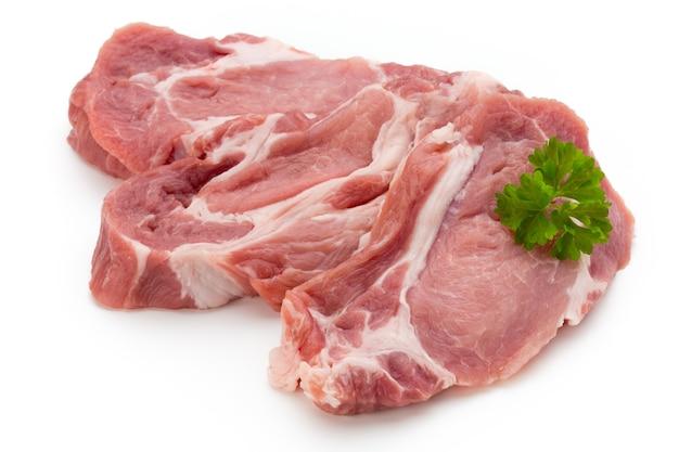 Plastry świeżej wieprzowiny wieprzowej na białym tle na białej powierzchni.