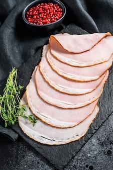 Plastry szynki wieprzowej z tymiankiem. mięso ekologiczne. czarne tło. widok z góry.