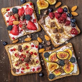 Plastry tostów pełnoziarnistych z twarogiem, różnymi owocami, nasionami i orzechami