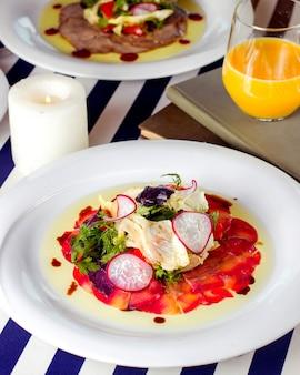 Plastry wędzonego łososia podawane z rzodkiewką sałatą i zieleniną