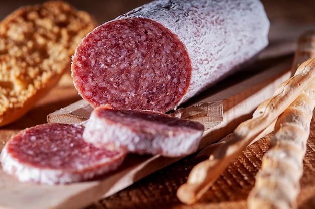 Plastry włoskiego salami z paluszkiem chlebowym
