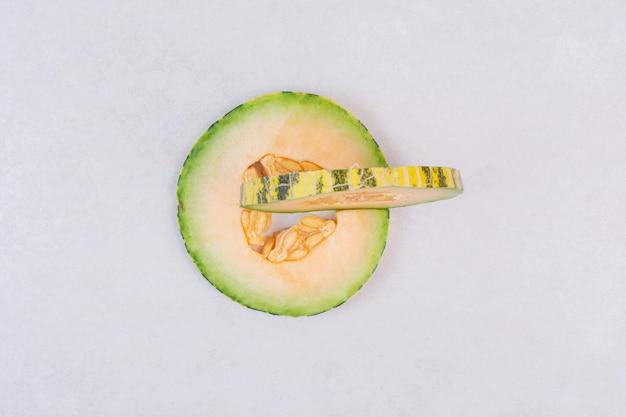 Plastry zielonego melona na białym stole.