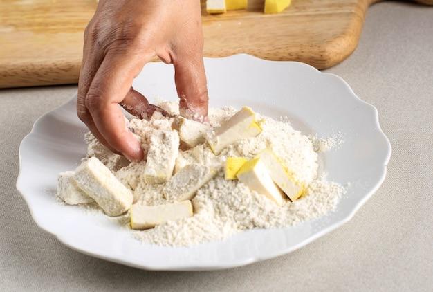 Plastry żółtej powłoki tofu z mąką, proces gotowania tworzenie chrupiącego tofu (tahu krispi) w kuchni