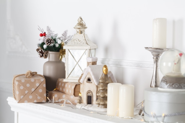 Płaszcz kominkowy jest ozdobiony na boże narodzenie girlandą, lampkami, kokardką i innymi dekoracjami.
