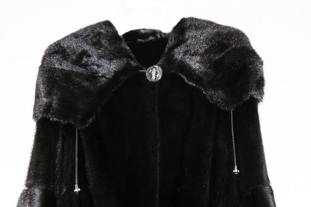 Płaszcz z norek czarny na białym tle. luksusowe naturalne futro. futro z kapturem