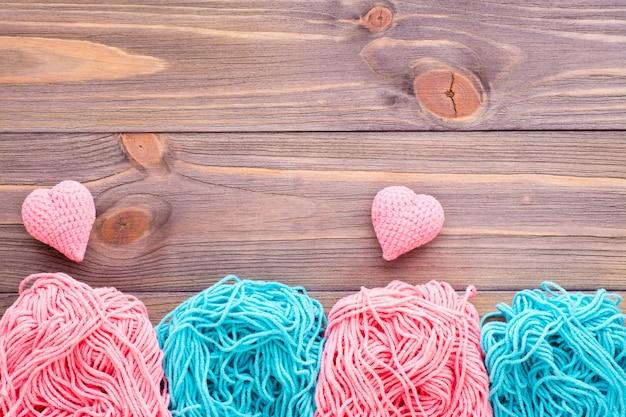 Plątaniny różowej i miętowej przędzy i dziewiarskie serca na drewnianym stole.