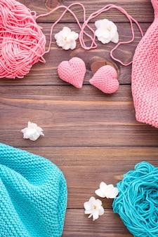 Plątaniny różowej i miętowej przędzy, snudy i dziewiarskie serca na drewnianym stole.