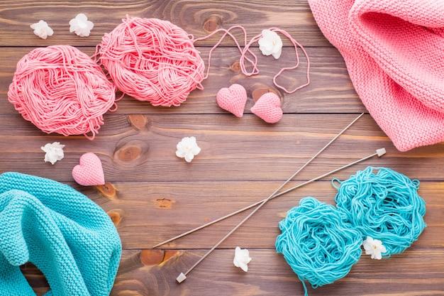 Plątaniny różowej i miętowej przędzy, snudy, igły i dziewiarskie serca na drewnianym stole.