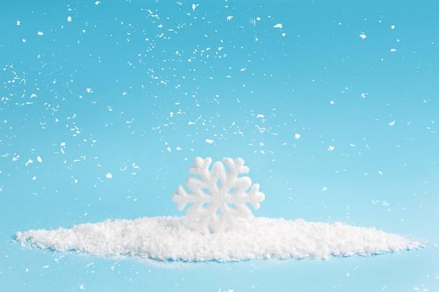 Płatek śniegu i śnieg na błękitnym tle. kompozycja świąteczna.