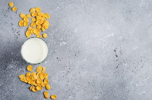 Płatki kukurydziane na betonowym tle i mleko w szklance. widok z góry.