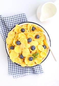 Płatki kukurydziane na śniadanie z jagodami na białym tle. selektywne skupienie.