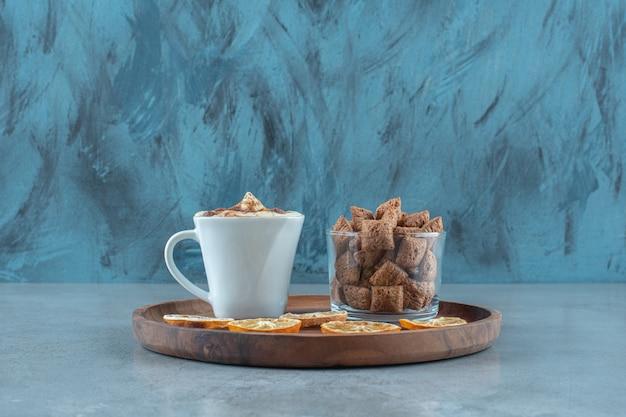 Płatki kukurydziane na szklance obok plasterków cytryny i filiżanki cappuccino na drewnianym talerzu, na niebieskim stole.