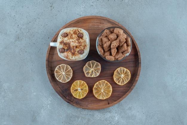 Płatki kukurydziane na szklance obok plasterków cytryny i filiżanki cappuccino na drewnianym talerzu, na niebieskim tle. zdjęcie wysokiej jakości