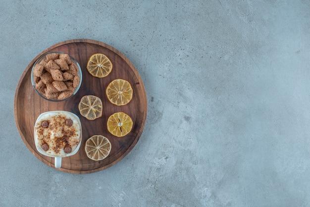 Płatki kukurydziane na szklance obok plasterków cytryny i filiżanki cappuccino na drewnianym talerzu, na niebieskim tle.