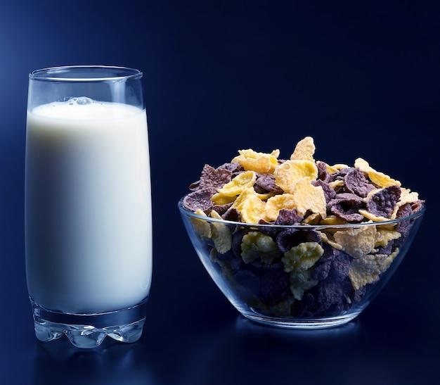 Płatki kukurydziane na talerzu i szklanka mleka
