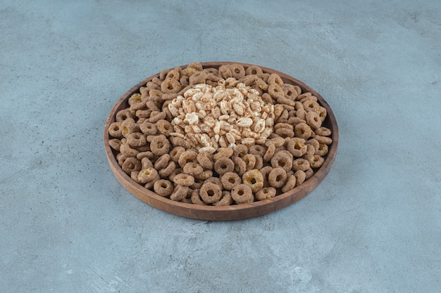 Płatki kukurydziane w drewnianym talerzu, na niebieskim tle. zdjęcie wysokiej jakości