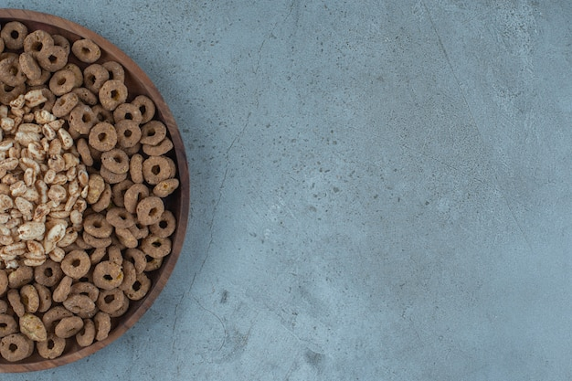 Płatki kukurydziane w drewnianym talerzu, na niebieskim tle.