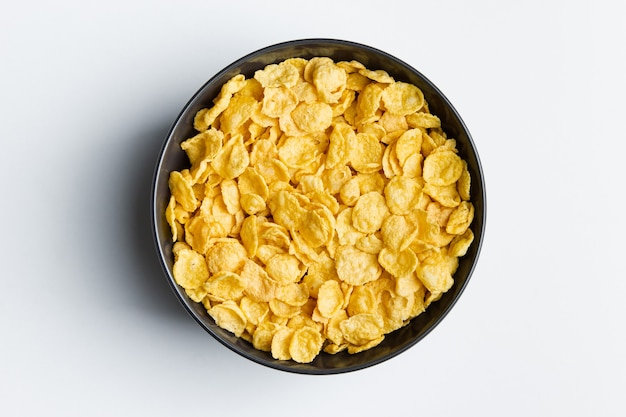 Płatki kukurydziane w misce na białym tle
