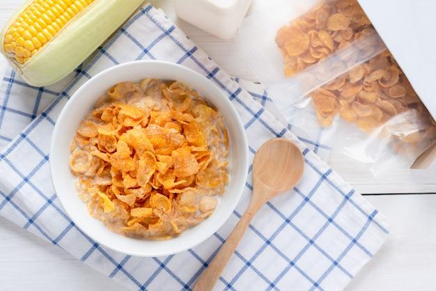Płatki kukurydziane w misce z mlekiem i płatkami zbożowymi