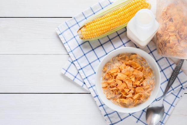 Płatki kukurydziane w misce z mlekiem i płatki zbożowe płatki kukurydziane w plastikowym opakowaniu