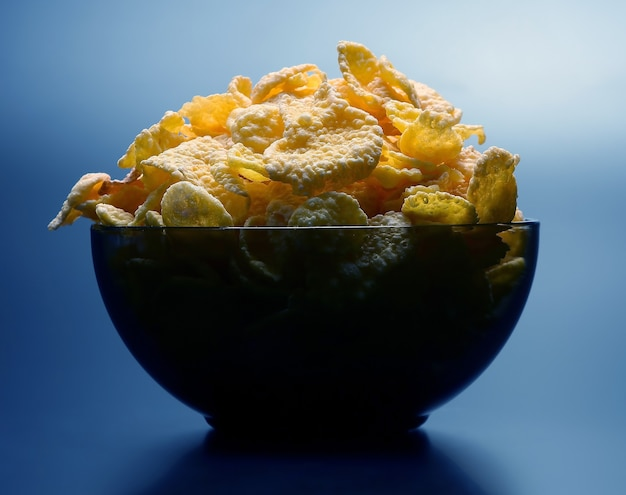 Płatki kukurydziane w naczyniu podświetlanym z góry. zdrowa i witaminowa żywność