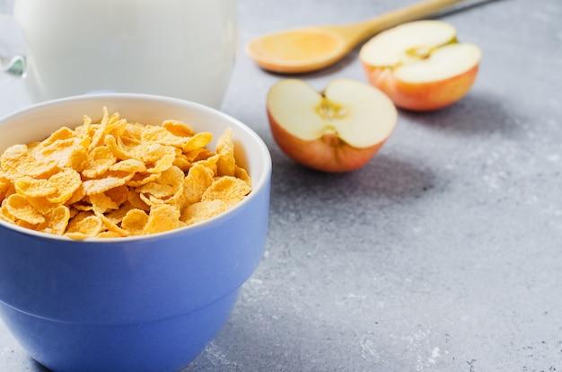 Płatki kukurydziane w niebieskim plasterku cup i apple. przydatne śniadanie rano. skopiuj miejsce