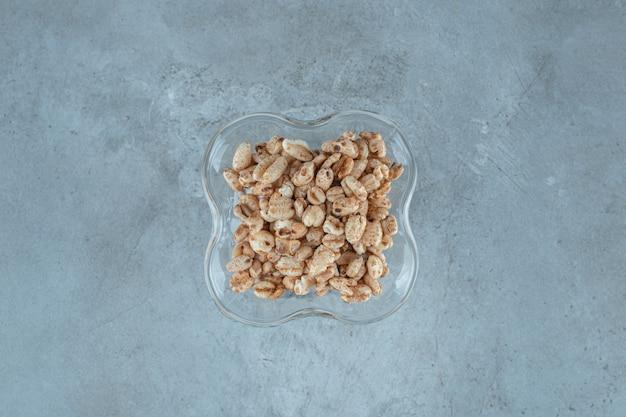 Płatki kukurydziane w szklance do kawy mleka, na niebieskim tle.