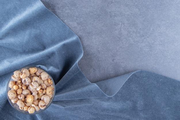 Płatki kukurydziane w szklanej misce na kawałku tkaniny, na marmurowym tle.