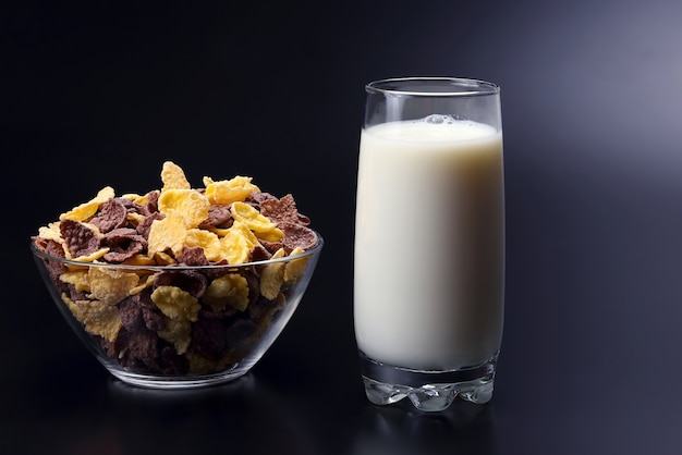 Płatki kukurydziane w talerzu i szklanka mleka