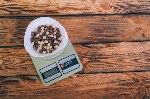 Płatki kukurydziane w talerzu na wadze na drewnianym.