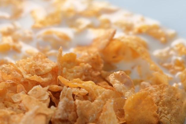 Płatki kukurydziane z lukrem cukrowym z mlekiem na śniadanie makro zbliżenie