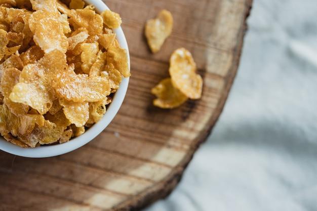 Płatki kukurydziane z miodem w białej misce na drewnianym stole. skopiuj miejsce
