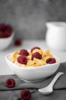 Płatki kukurydziane z mlekiem i malinami na białym stole