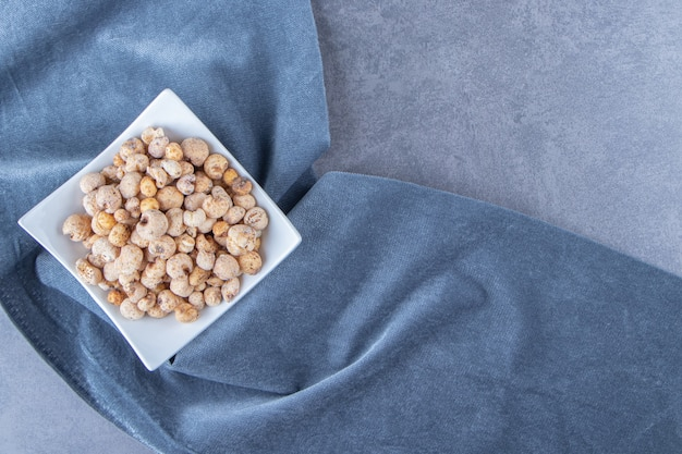 Płatki kukurydziane z musli w misce na kawałku materiału, na marmurowym stole.