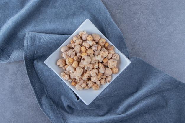 Płatki kukurydziane z musli w misce na kawałku materiału, na marmurowym tle.