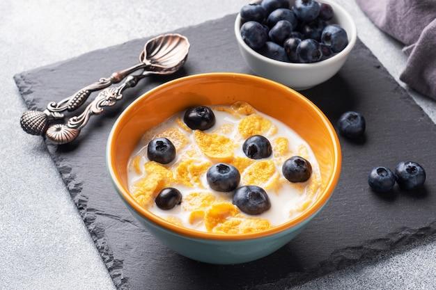 Płatki kukurydziane z naturalnych zbóż ze świeżymi jagodami, miodem i mlekiem