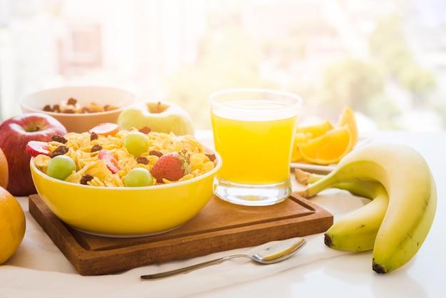Płatki kukurydziane z owocami; sok ze szkła na desce do krojenia nad stołem