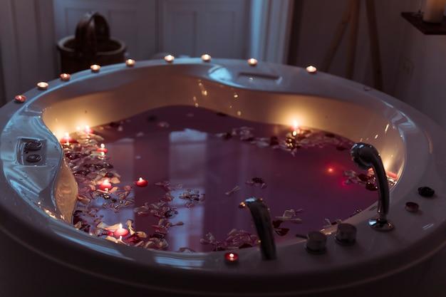 Płatki kwiatów w wannie spa z wodą i palenie świec na krawędziach