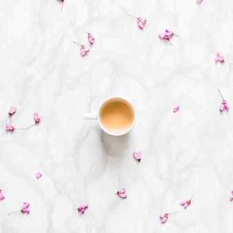 Płatki kwiatów z filiżanką kawy