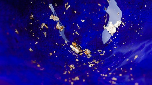 Płatki metalu ze złotej folii na niebieskim tle panoramy z ceramicznej emalii