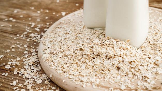 Płatki owsiane i butelka świeżego mleka na desce. drewniane rustykalne tło