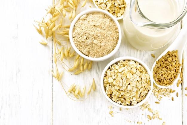 Płatki owsiane i mąka w miseczkach, ziarno w łyżce, mleko owsiane w szklanym dzbanku i dojrzałe łodyżki owsiane na tle drewnianej deski z góry