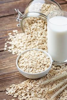 Płatki owsiane i szklankę mleka na drewnianym stole.