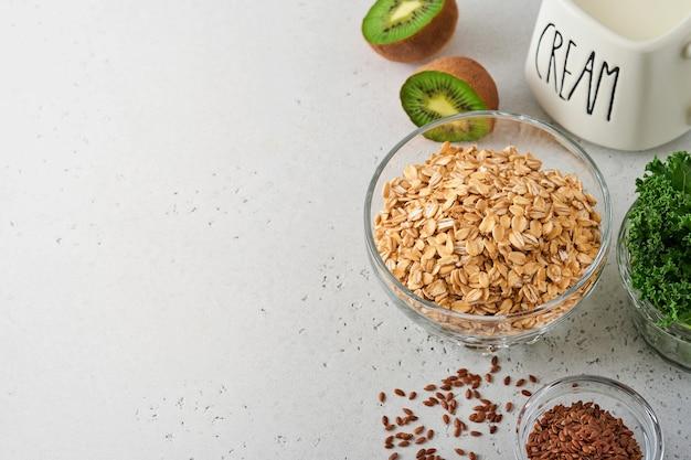 Płatki owsiane, jarmuż, nasiona kiwi i chia, składniki kremów do sporządzania koktajli detoksykacyjnych