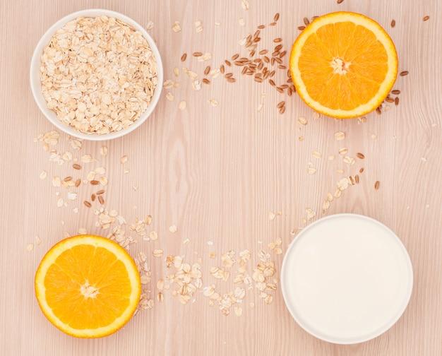 Płatki owsiane, mleko w białej misce i przepołowione pomarańcze na drewnianym tle