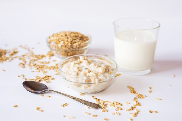 Płatki owsiane na talerzu ze szklanką mleka i łyżką na białej powierzchni.