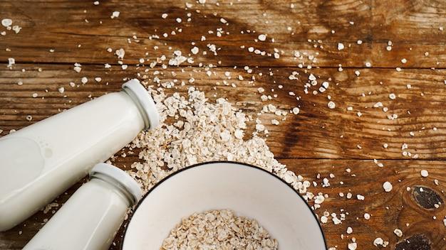 Płatki owsiane w białej misce i butelkach świeżego mleka. drewniane rustykalne tło