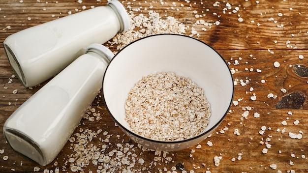 Płatki owsiane w białej misce i butelki świeżego mleka. drewniana powierzchnia rustykalna